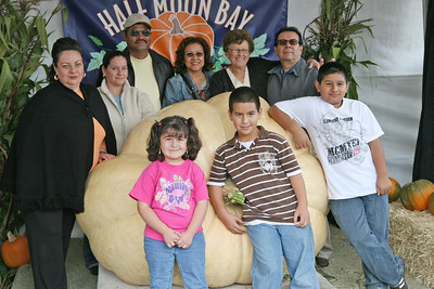 The Perez, Riario and TomozouzFamilies from Martinez and Napa pose for a picture with this year«s winning pumpkin by Thad Starr or Oregon, which weighed in at 1,524 lbs. The Art & Pumpkin Festival celebrated its 37th year over the weekend in Half Moon bay, called the ÒWorld Pumpkin CapitalÓ. Aside from pumpkins on display, the public enjoyed 250 booths with the artwork of local artists, live music, food, local wine and of course pumpkin pie. Activities during the festival included a costume contest, a visit to a haunted house, a pumpkin run/walk, among other things.