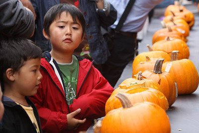 Hikavn Umeyama 5, (far left) and his brother Akira Umeyama 7 stop to admire the entries in the  public pumpkin carving contest. The Art & Pumpkin Festival celebrated its 37th year over the weekend in Half Moon bay, called the ÒWorld Pumpkin CapitalÓ. Aside from pumpkins on display, the public enjoyed 250 booths with the artwork of local artists, live music, food, local wine and of course pumpkin pie. Activities during the festival included a costume contest, a visit to a haunted house, a pumpkin run/walk, among other things.