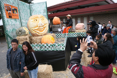 People pose and take pictures as they admire a giant carved pumpkin created by Farmer Mike Valladao of San Jose. The Art & Pumpkin Festival celebrated its 37th year over the weekend in Half Moon bay, called the ÒWorld Pumpkin CapitalÓ. Aside from pumpkins on display, the public enjoyed 250 booths with the artwork of local artists, live music, food, local wine and of course pumpkin pie. Activities during the festival included a costume contest, a visit to a haunted house, a pumpkin run/walk, among other things.