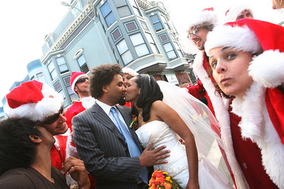 Sennai and Ruth Mussie, newly weds who were on a romantic walk on the streets of San Francisco in North Beach are congratulated by hundreds of Santas in the street.  The Cacophony Society staged the first SantaCon (Also known as Santa Archy) in San Francisco in 1994 by which several dozen people dressed in cheap Santa costumes took the city by storm performing publicly on the street and in bars.  By 2003, the event grew into a phenomenon participated in 30 cities, 5 countries with hundreds of SantaÕs at each event.  This YearÕs Santacon gathered at Pier 39 at 10am on Saturday.  Approximately 400 SantaÕs took the ferry to Oakland while the remaining approximate 250 made their way pub-crawling through FishermanÕs Warf and into Grant Street on North Beach.  At about 3:20pm SF Police arrived to control the crowd and maintain safety but the street party kept going.  Eventually the massive crowd of mischievous from both Oakland and San Francisco gathered at The Irish Bank and Union Square for one final round of fun and melee.