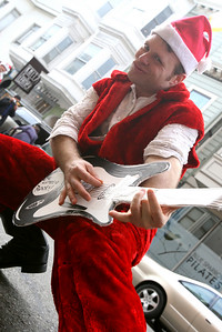 "Aaron Rabideau as ""Santa Rock"" plays his cardboard guitar on the streets of Noth Beach. The Cacophony Society staged the first SantaCon (Also known as Santa Archy) in San Francisco in 1994 by which several dozen people dressed in cheap Santa costumes took the city by storm performing publicly on the street and in bars.  By 2003, the event grew into a phenomenon participated in 30 cities, 5 countries with hundreds of SantaÕs at each event.  This YearÕs Santacon gathered at Pier 39 at 10am on Saturday.  Approximately 400 SantaÕs took the ferry to Oakland while the remaining approximate 250 made their way pub-crawling through FishermanÕs Warf and into Grant Street on North Beach.  At about 3:20pm SF Police arrived to control the crowd and maintain safety but the street party kept going.  Eventually the massive crowd of mischievous from both Oakland and San Francisco gathered at The Irish Bank and Union Square for one final round of fun and melee."