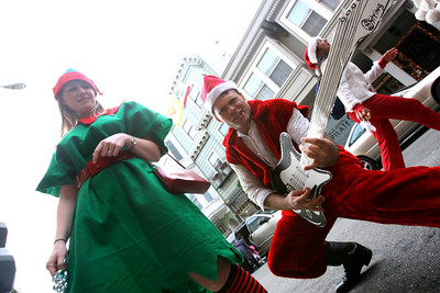 "Aaron Rabideau as ""Santa Rock"" with one of his trusty elves, plays his cardboard guitar on the streets of Noth Beach.  The Cacophony Society staged the first SantaCon (Also known as Santa Archy) in San Francisco in 1994 by which several dozen people dressed in cheap Santa costumes took the city by storm performing publicly on the street and in bars.  By 2003, the event grew into a phenomenon participated in 30 cities, 5 countries with hundreds of SantaÕs at each event.  This YearÕs Santacon gathered at Pier 39 at 10am on Saturday.  Approximately 400 SantaÕs took the ferry to Oakland while the remaining approximate 250 made their way pub-crawling through FishermanÕs Warf and into Grant Street on North Beach.  At about 3:20pm SF Police arrived to control the crowd and maintain safety but the street party kept going.  Eventually the massive crowd of mischievous from both Oakland and San Francisco gathered at The Irish Bank and Union Square for one final round of fun and melee."