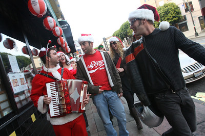 Andrew Shubov (acordion) Crow Bar Katie, (middle) and Ben Martin (Coca Cola T-shirt) sing Madonna«s Like a Prayer as the crowd of Santas walk down Colubus Ave. en route to the next bar.  The Cacophony Society staged the first SantaCon (Also known as Santa Archy) in San Francisco in 1994 by which several dozen people dressed in cheap Santa costumes took the city by storm performing publicly on the street and in bars.  By 2003, the event grew into a phenomenon participated in 30 cities, 5 countries with hundreds of SantaÕs at each event.  This YearÕs Santacon gathered at Pier 39 at 10am on Saturday.  Approximately 400 SantaÕs took the ferry to Oakland while the remaining approximate 250 made their way pub-crawling through FishermanÕs Warf and into Grant Street on North Beach.  At about 3:20pm SF Police arrived to control the crowd and maintain safety but the street party kept going.  Eventually the massive crowd of mischievous from both Oakland and San Francisco gathered at The Irish Bank and Union Square for one final round of fun and melee.