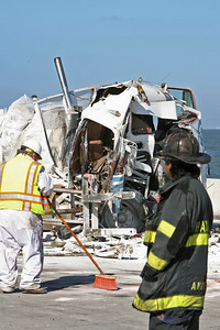 A cleanup crew works to soak up fuel and debree from the road while the remains of one of the vehicles in the crash is seen in the background.  2 big rigs and one flat bed collided on the San Mateo Bridge west bound.  Know body died but three injuries were reported with one victim transported by helicopter.  Traffic westbound was closed until 11:30am when one lane was re-opened.  Full traffic restored by 1pm.