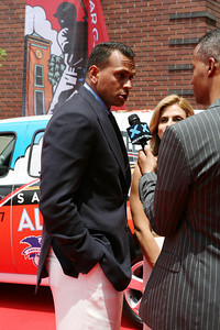 Alex Rodriguez of the New York Yankees conducts an interview as he walks into AT&T park on the red carpet during the parade entrance for the players on the day of the All Star game.