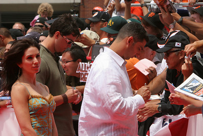 Jorge Posada of the New York Yankees signs autographs as he walks into AT&T park on the red carpet during the parade entrance for the players on the day of the All Star game.