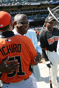 Dusty Baker hugs Ichiro while Bonds stands in the background.