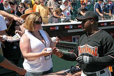 Bonds signs autographs for the public during batting practice.