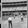 Four men playing baseball at the Dodgers Stadium construction site in Chavez Ravine, Los Angeles