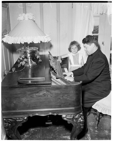 Pastor of San Gabriel Mission plays antique piano, 1952