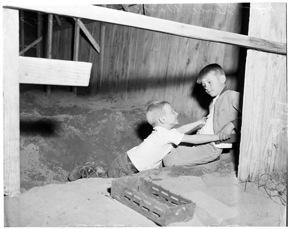 Little boy rescued after he had fallen in hole, 1957