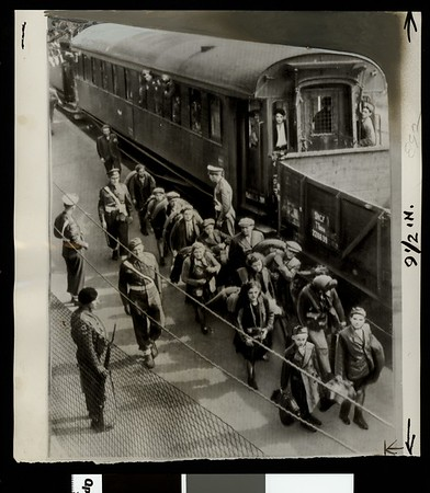 Jewish refugees are guarded by British troops as they leave train at Kuechnitz, Germany, 1947