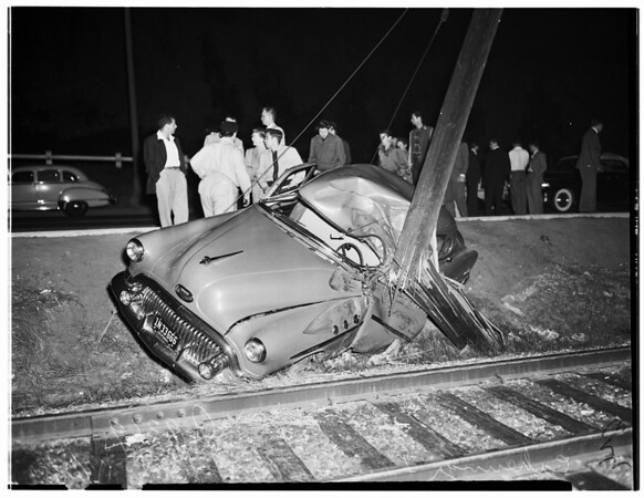 Accident...Cahuenga Freeway...General views of car against utility pole and between two guy wires on Pacific Electric Tracks, 1951