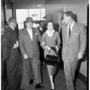 Jane Cabanne in court after having fainted following issuance of order restraining husband, 1957