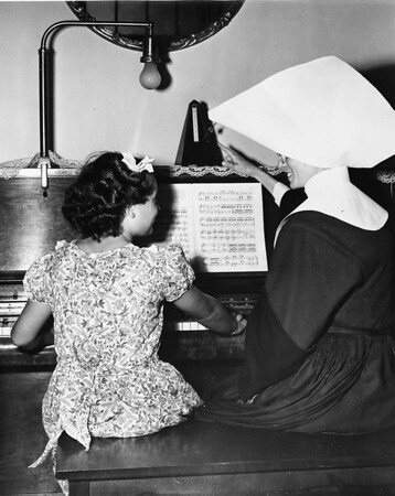 A nun of the Los Angeles Orphanage gives piano lessons to a little girl, 1950