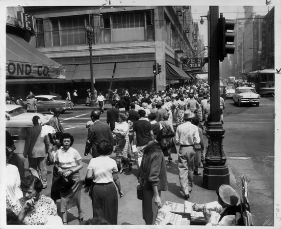 The crowded streets of Downtown as people walk across the crosswalk of Seventh Street and Broadway, ca.1956