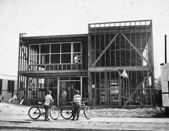 Two children with bicycles watch the construction of a youth center, 1949