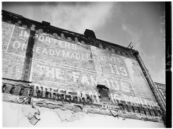 "Old sign discovered...old building at 221 South Spring Street torn down reveals ""Gay Nineties"" sign of famous clothing firm next door, 1951"