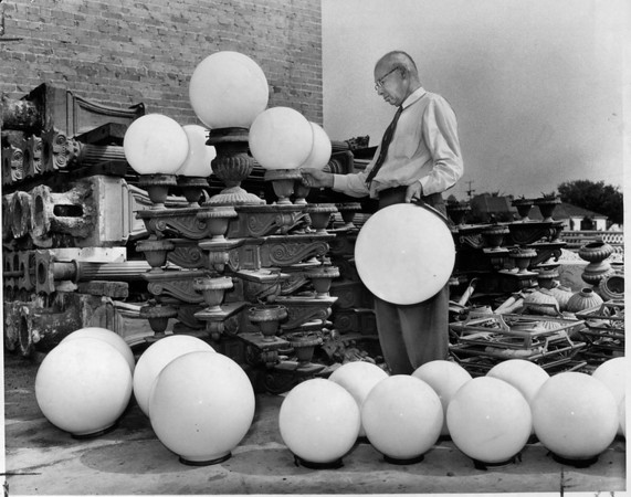 J.A. Lindhardt, examines the ornate street light fixtures, Los Angeles, 1959