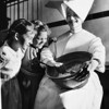 Two girls of the Los Angeles Orphanage watch Sister Elizabeth mix cake batter, 1951