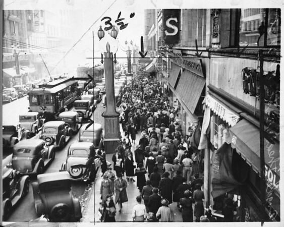 Busy Broadway packed with automobiles and streetcars and sidewalk packed with pedestrians, ca.1940