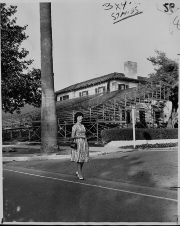 Tournament of Roses stenographer Joan Pulcifer passes grandstands along South Orange Grove Boulevard while going to work, 1961