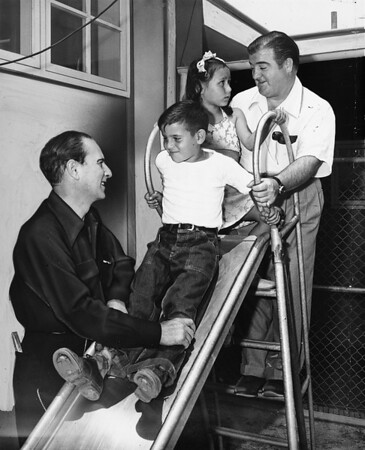 Abbott and Costello play with children on a slide, East Los Angeles Recreation Center, 1948
