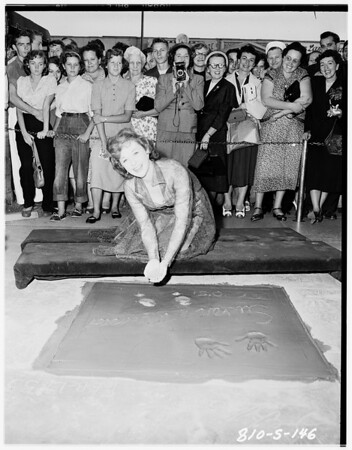Susan Hayward putting footprints in cement at Grauman's Chinese Theater, 1951