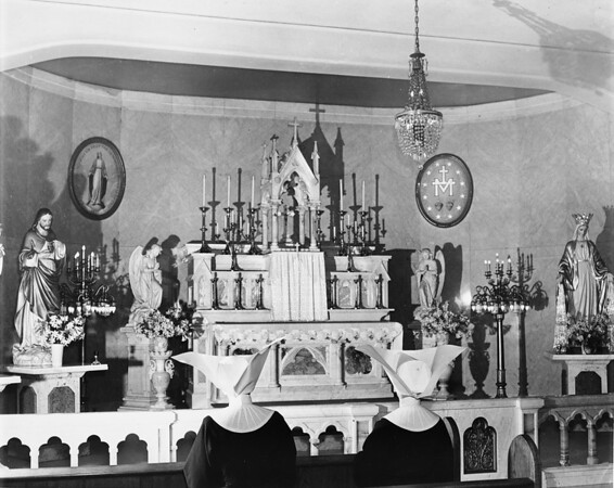 Two nuns of the Daughters of Charity pray to a shrine of Jesus Christ, 1950