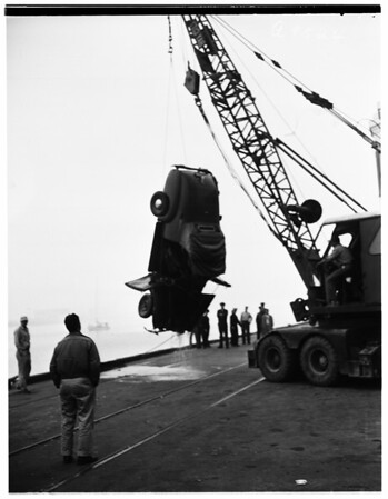 Auto falls into Pacific Ocean and is lifted out with crane...,1952
