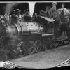 Seventeen people gathered around or on a working scale model of a railroad steam engine, 1925