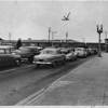 Autos on Los Feliz Rd., Glendale, held up while freight train passes, 1953