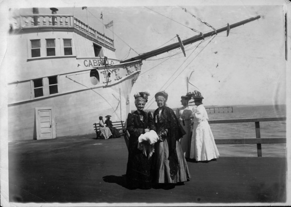 "Mrs. Anna M. Averil and Madame Caroline M. Severance standing in front of the ""ship"" Cabrillo at the Venice Amusement Pier in Venice, California, ca.1910"