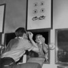 A student looking in a mirror applies grease paint to his face in the Pasadena Playhouse, 1952