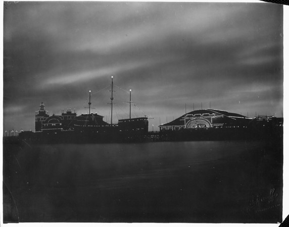View over the water of the amusement park and pier at Venice Beach lit up at night, [s.d.]
