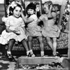 Three little girls of the Los Angeles Orphanage play with colorful hair ribbons, 1953