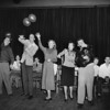 Teenagers at a church party play shot put with balloons, 1949