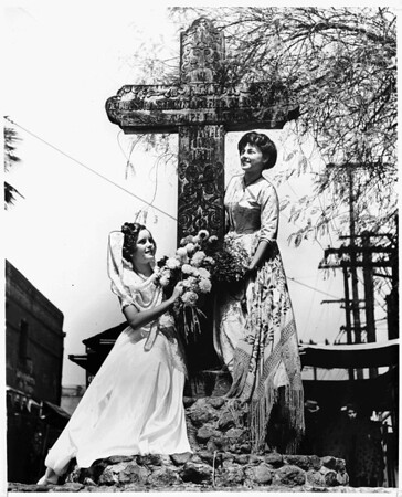 Two women pose around the cross at the entrance to Olvera St., Los Angeles, 1943