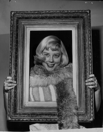 Mrs. Katie Hansen shows fur neckpiece and antique frame, Pasadena, 1953