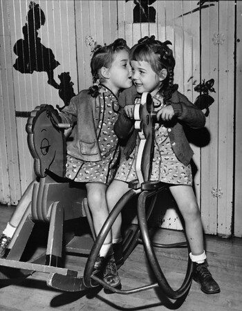 Two girls at the Los Angeles Orphanage on hobby horses, 1949