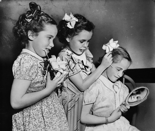 Three little girls of the Los Angeles Orphanage with hair ribbons, 1948