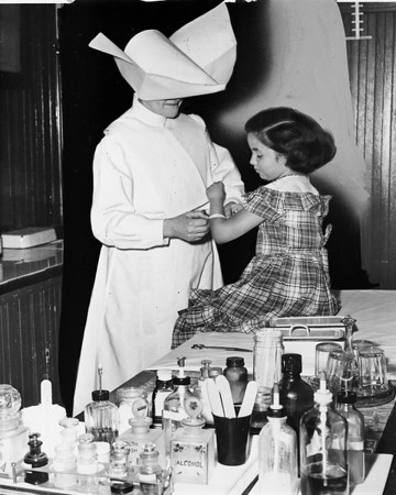 Sister Esther attends to a little girl, Jackie Barnes, 1950