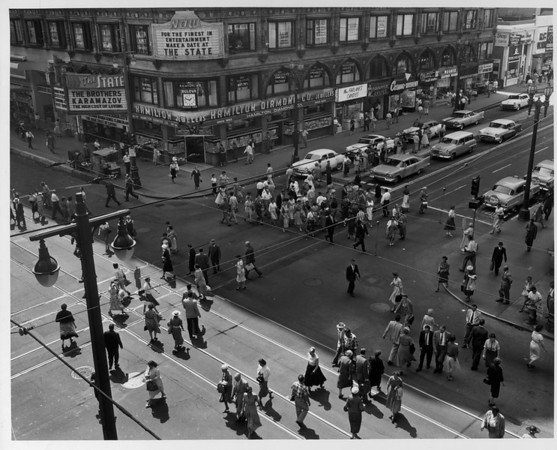 A high-angle view of the entire corner of Seventh street and Broadway crowded with people and cars with The State Theater in the background