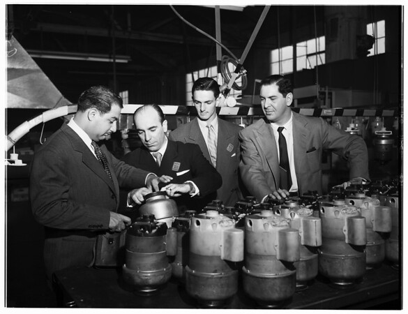 Examining Waste King pulverators on assembly line at Given Plant in Vernon, 1952
