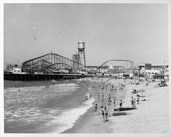 People frolic on the beach near the roller coaster in the amusement park at Venice Beach, 1940
