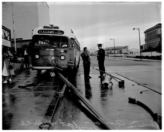Bus versus auto accident at 1st and Hill Streets - fire hydrant in the street - wreckage of signal is under bus, 1958