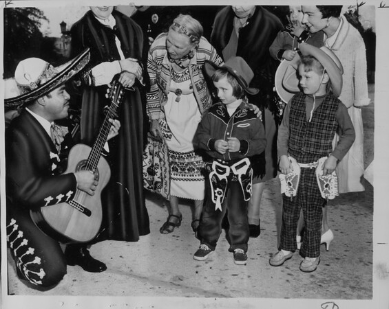 Don Juan Benavides singing to children in City Hall plaza, Pasadena, 1961