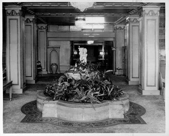 "Interior of a hotel showing a fountain in a corridor to the ""Embassy - Colonial Rooms"""
