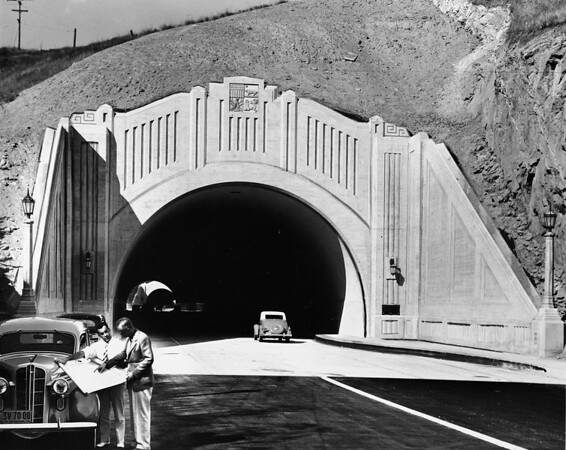 Figueroa Street portal with two men surveying blueprint on car hood at First Street