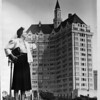 Woman standing in the foreground on the lawn in front of the 15-story Villa Riviera Apartment building with an octagonal pointed tower on top, Long Beach, California